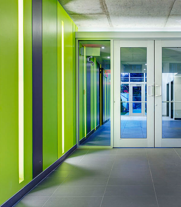 Entrance to the condo building with green walls and lighting